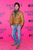 Matthew Settle in a brown leather jacket.