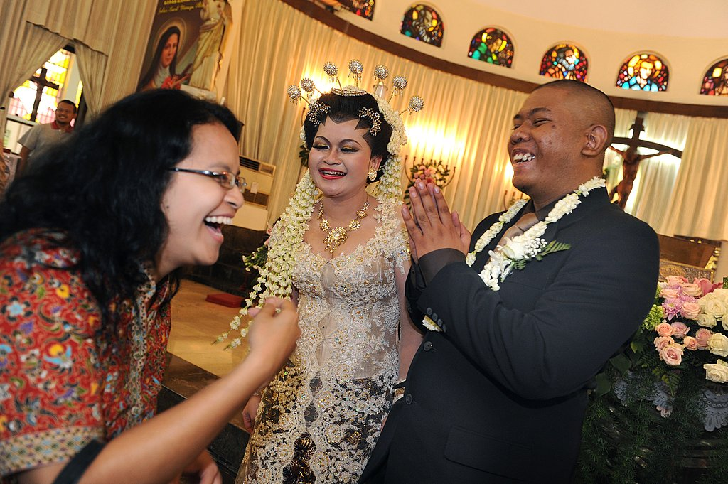 Members of Indonesia's minority Christian community, groom Radityo Soenarto and bride Caroline Dwi Lestari, are greeted by family following their wedding ceremony.