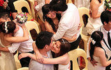 Newlywed couples share a kiss during a mass wedding.
