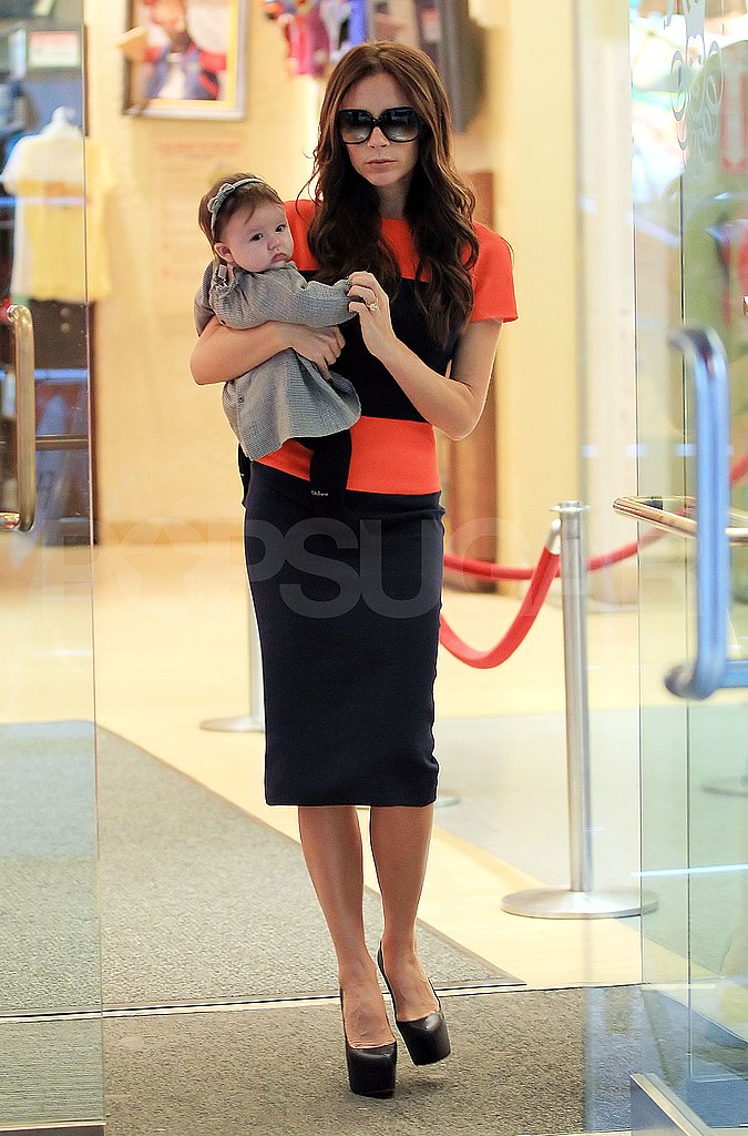Victoria Beckham carried daughter Harper Beckham out of NYC's FAO Schwarz.