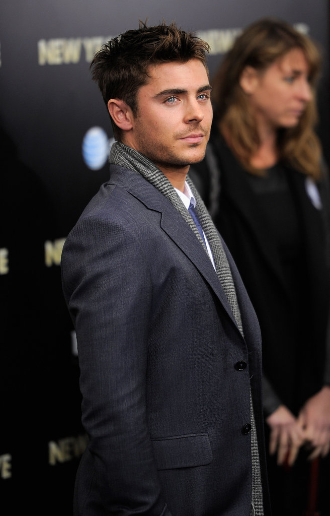 Zac Efron accessorized with a scarf on the carpet.