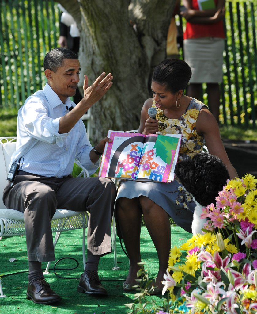 Bo helps Barack and Michelle read a book to a crowd of kids.