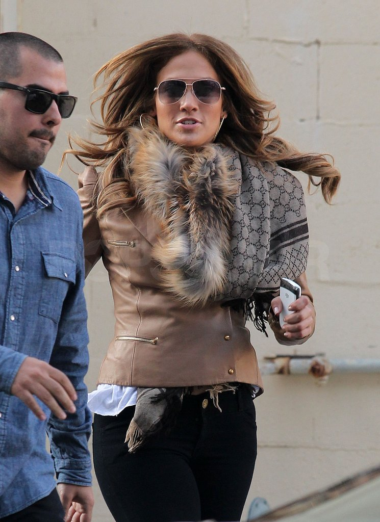 J Lo left a jewelry store dressed in a fur-lined jacket and Gucci scarf.