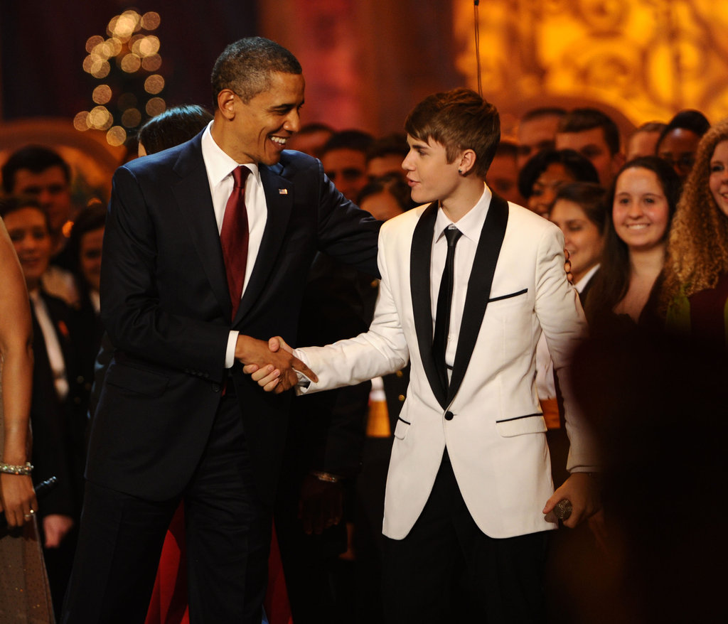 Justin Bieber and Barack Obama shake hands.