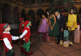 Kids in elf costumes greet the Obamas.