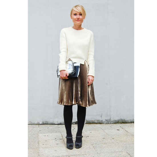 A gold pleated skirt — spotted on the street during Spring 2012 Paris Fashion Week — looks chic for day when topped with a cozy cream sweater and opaque black tights. Gray Mary Janes keep the look soft, and a silver Alexander Wang clutch adds contrast.   Shop the look:  Photo: Stylesight