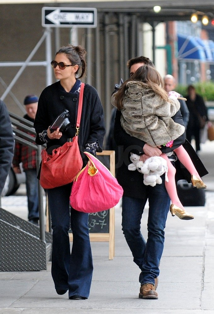 Suri cuddled close to Tom on a walk through the city.