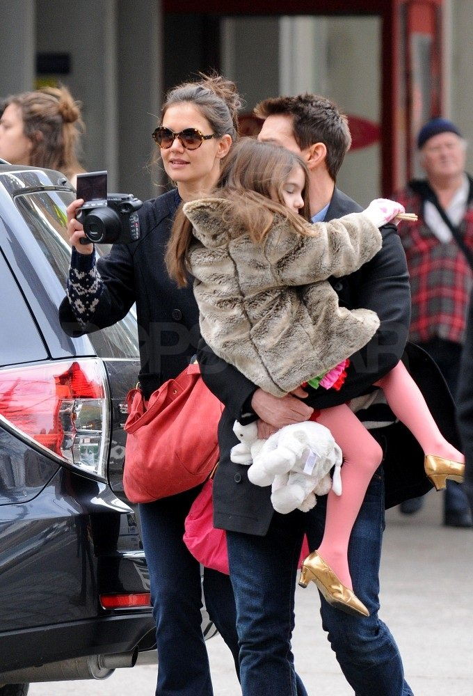 Suri Cruise wore pink tights and carried a stuffed toy.