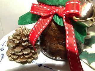 Christmas pudding in jar gift-wrapped with seasonal colours and a little bell.