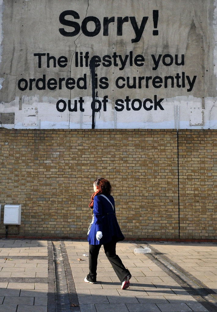 A woman walks by Banksy's latest.