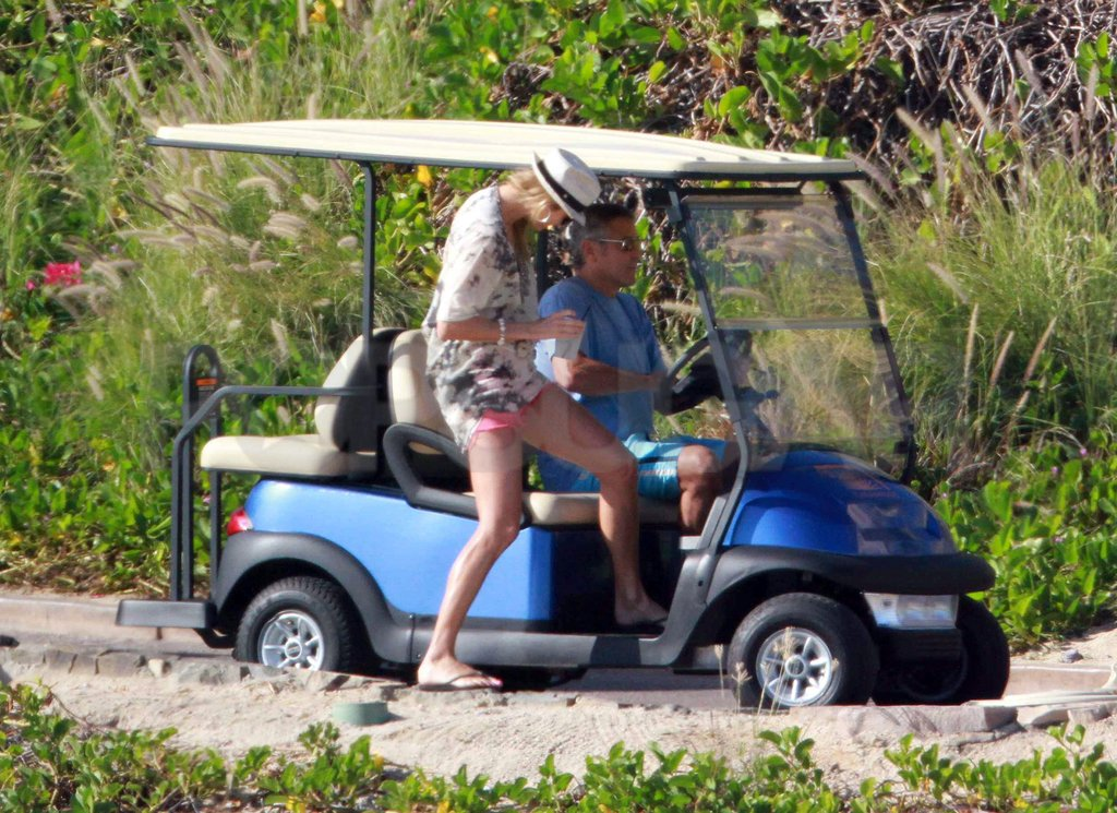Stacy Keibler steadied her drink while getting into a golf cart with George Clooney.