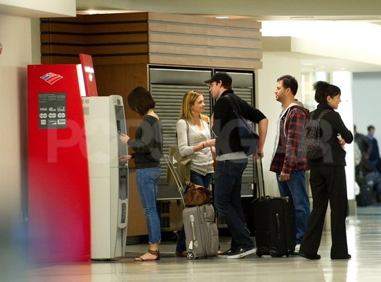Emily Blunt hit up an ATM before boarding a flight with John Krasinski, Jimmy Kimmel and Molly McNearney.
