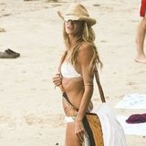 Elle Macpherson wore a cross body bag to the beach over her white bikini.