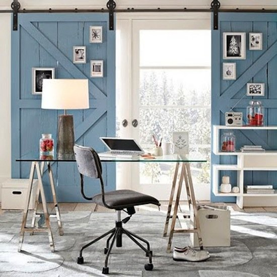Use sliding barn doors adorned with framed art instead of curtains for privacy and lighting control in an office.  Source