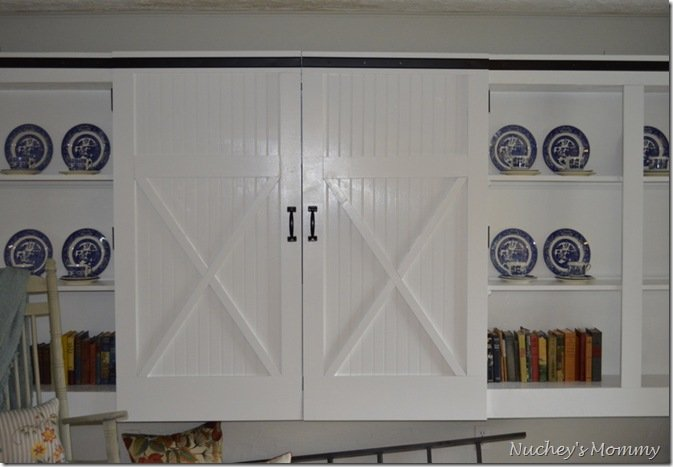 These DIY barn doors are adorned with black trim that imitates classic hardware. Instead of sliding, these doors can be pulled to reveal a closet space. Learn how to add molding and faux hardware trim to everyday doors to achieve this sliding barn door look!   Source