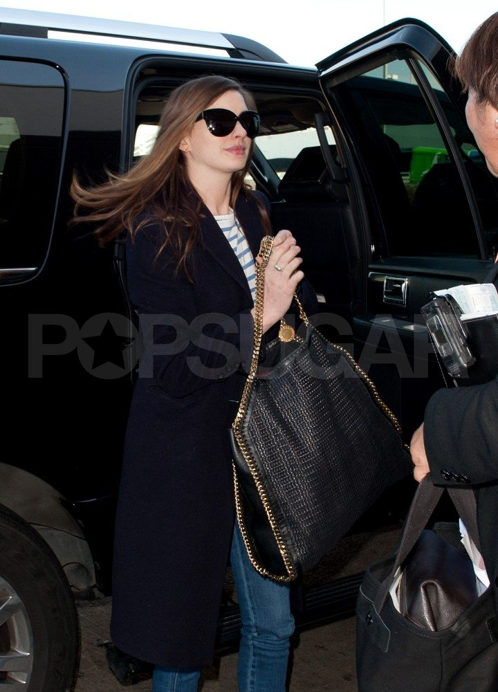Anne Hathaway carried her own bag into the airport.