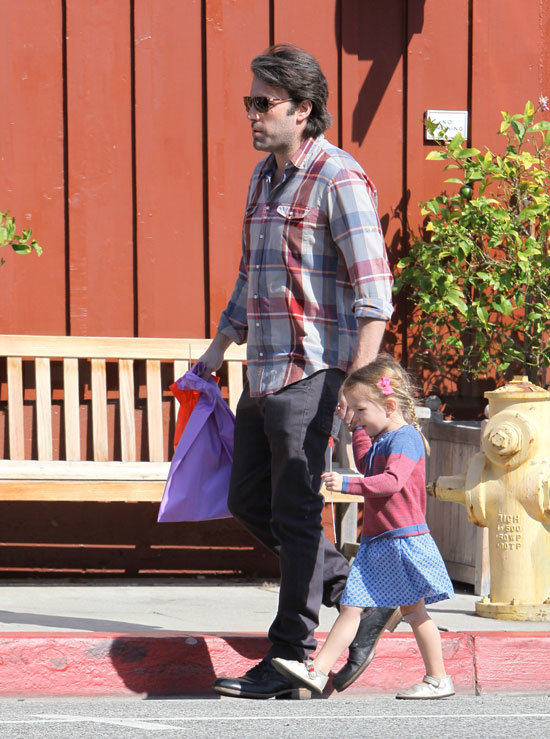 Ben carried a bag of gifts while Seraphina focused on her lollipop.