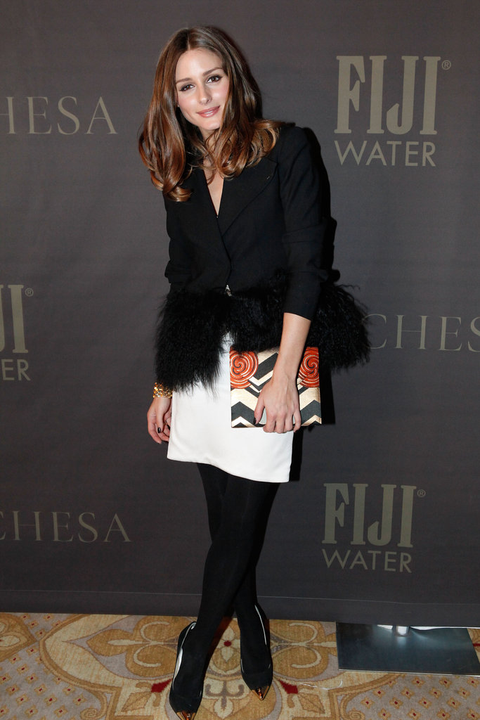 Olivia styled a feather-trimmed blazer with a white skirt and printed clutch at the Marchesa show.