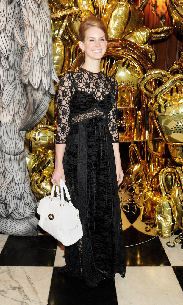 For her performance at the Mulberry afterparty, Lana continued her obsession with sheer in black lace — sexy! — and held on tight to her Mulberry Del Rey bag.         Longsleeve Tops by Betsey JohnsonSandals by KORS