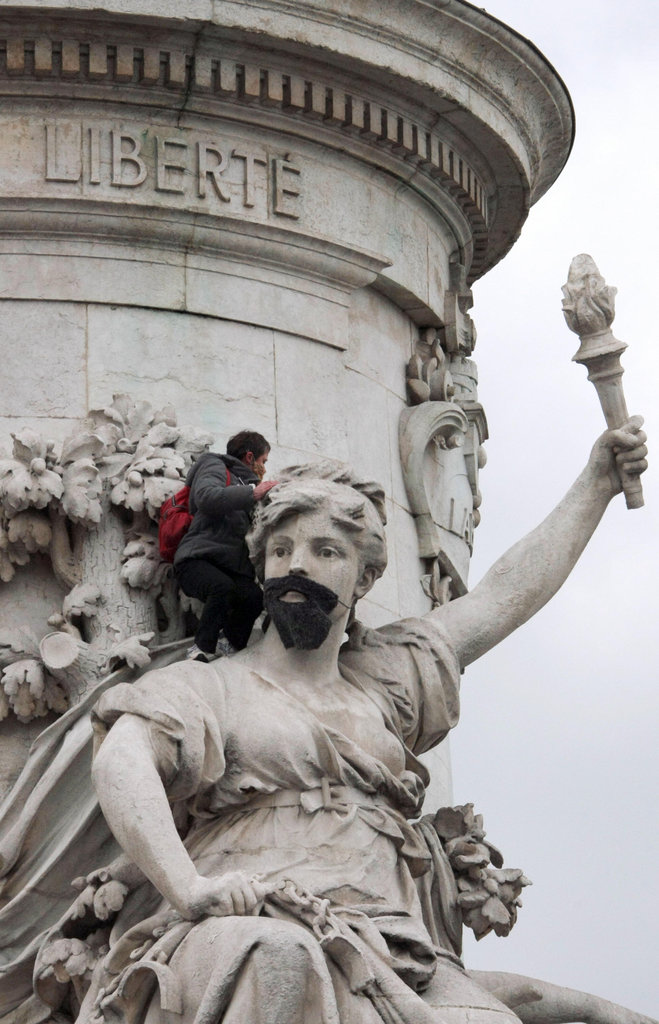 A woman from La Barbe attaches a beard to a French national symbol on International Women's Day in 2009.