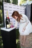 Emma Stone signing a bottle of Moet champagne.  Image courtesy of Alex Berliner
