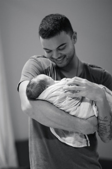 Guy holds his new son Hudson.