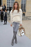 Dasha Zhukova paired gray knee-high boots with matching jeans, a cozy fringed sweater, and Celine bag at the Christian Dior show.