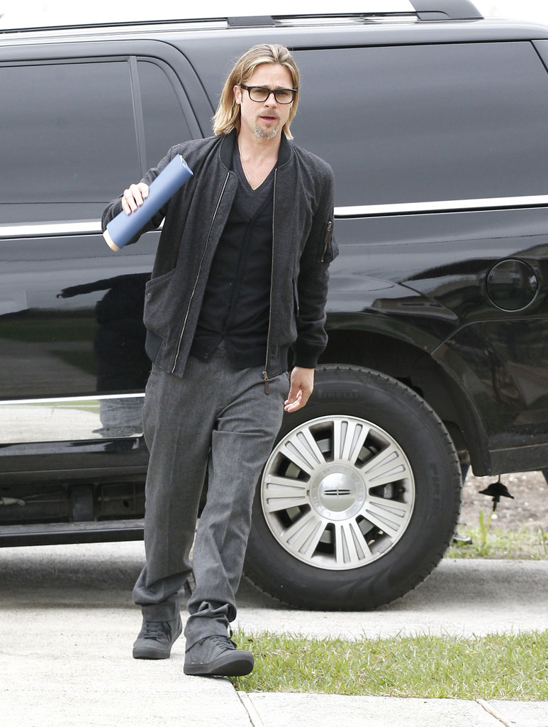 Brad Pitt carried a blue folder full of papers with him.