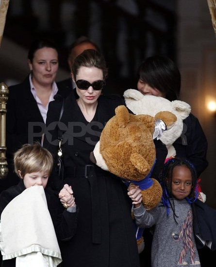 Angelina Jolie holding Shiloh and Zahara's hands.
