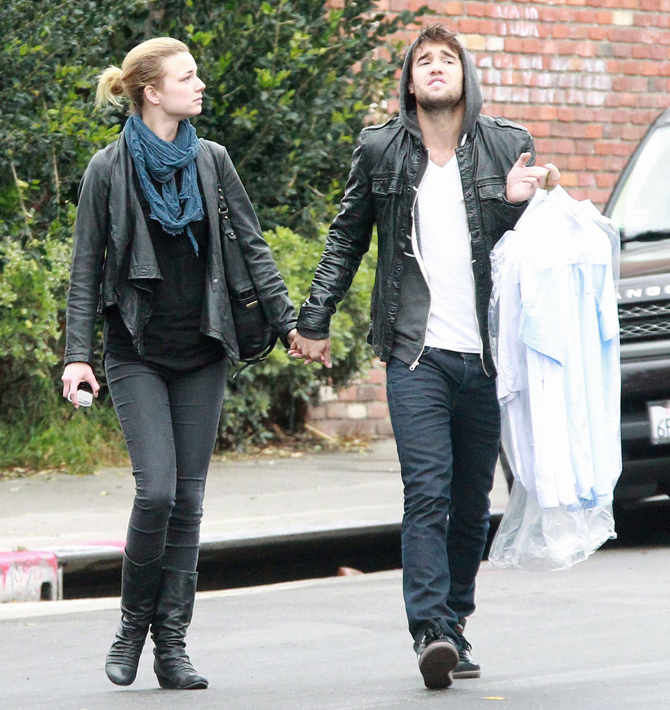 Revenge's Emily VanCamp and Joshua Bowman holding hands.
