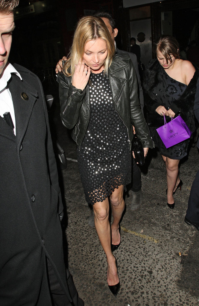 Kate Moss wearing a black dress and leather jacket.