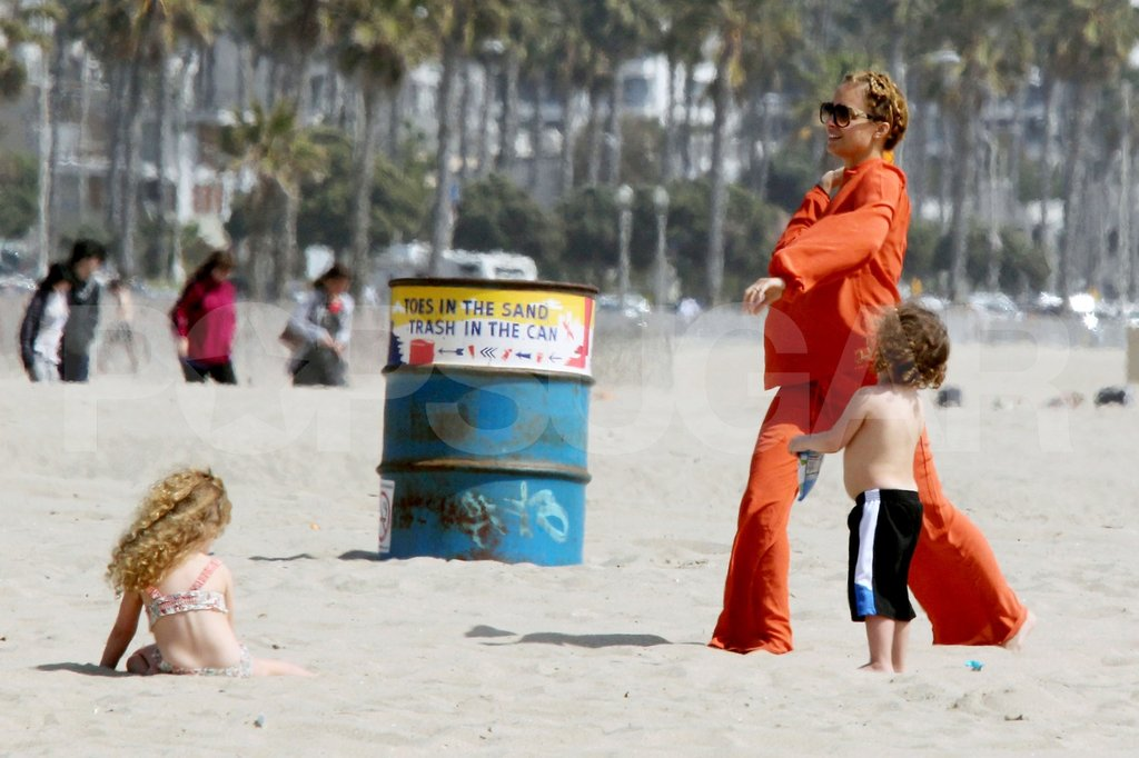 Nicole Richie wearing an all-orange ensemble on the beach with Harlow and Sparrow.