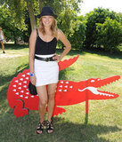 Malin Akerman posted up in the sun at Lacoste in a mini and a festival-fitting hat.
