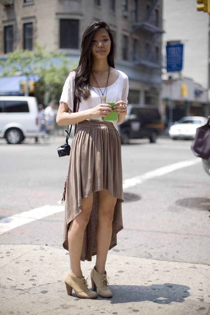 For a laid-back take, style your asymmetrical-hem skirt with loose basics and layered necklaces. Photo courtesy of Phil Oh