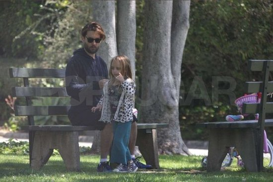 Ruby Maguire and Tobey Maguire lounged on a park bench.