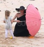 Angelina Jolie set up a pink umbrella while chatting with Vivienne.