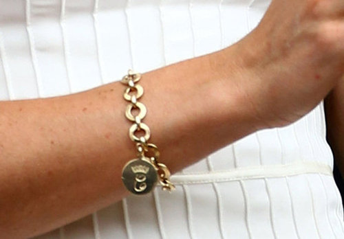 "A close-up on Kate's gold tennis bracelet (spotted on her at Wimbledon) — it's engraved with a crowned ""C."""