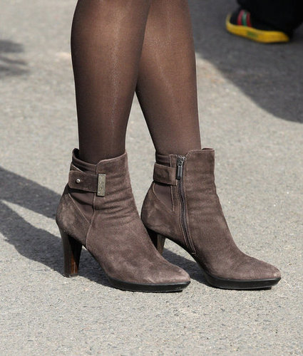 A close-up of Kate's heeled suede brown booties.
