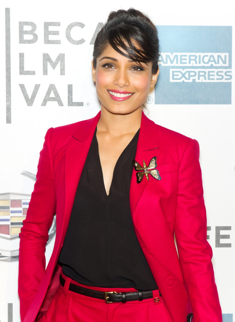 Freida Pinto added a whimsical touch to her red Gucci suit with a black and gold butterfly brooch.