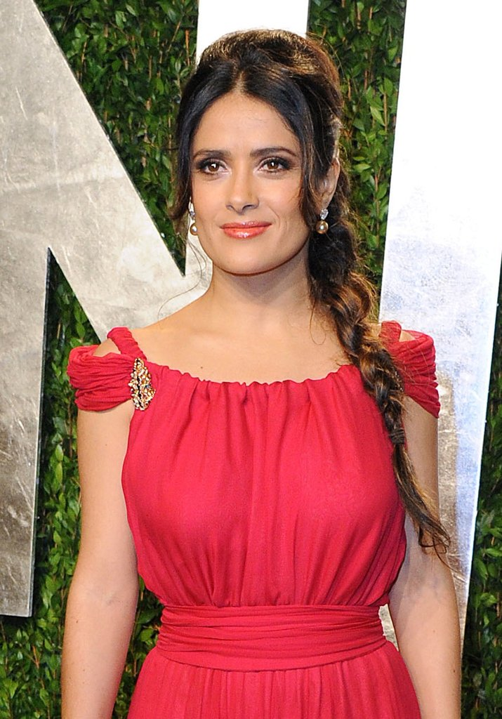 Salma Hayek accessorized her red Yves Saint Laurent gown with a gold and emerald brooch at the Vanity Fair Oscar party.