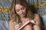 Miley writing in her diary.  6809703