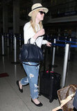 Dakota Fanning looked chic while traveling in a wide-brimmed straw hat and boyfriend jeans. It's the perfect way to look polished before (or after) a long flight.