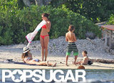 Miranda Kerr sprawled out in the sand with an eye on Flynn.