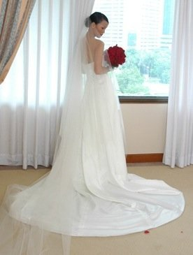 Fab reader Mindorena stunned in a liquid white wedding creation, and the ultralong veil polished off her look.