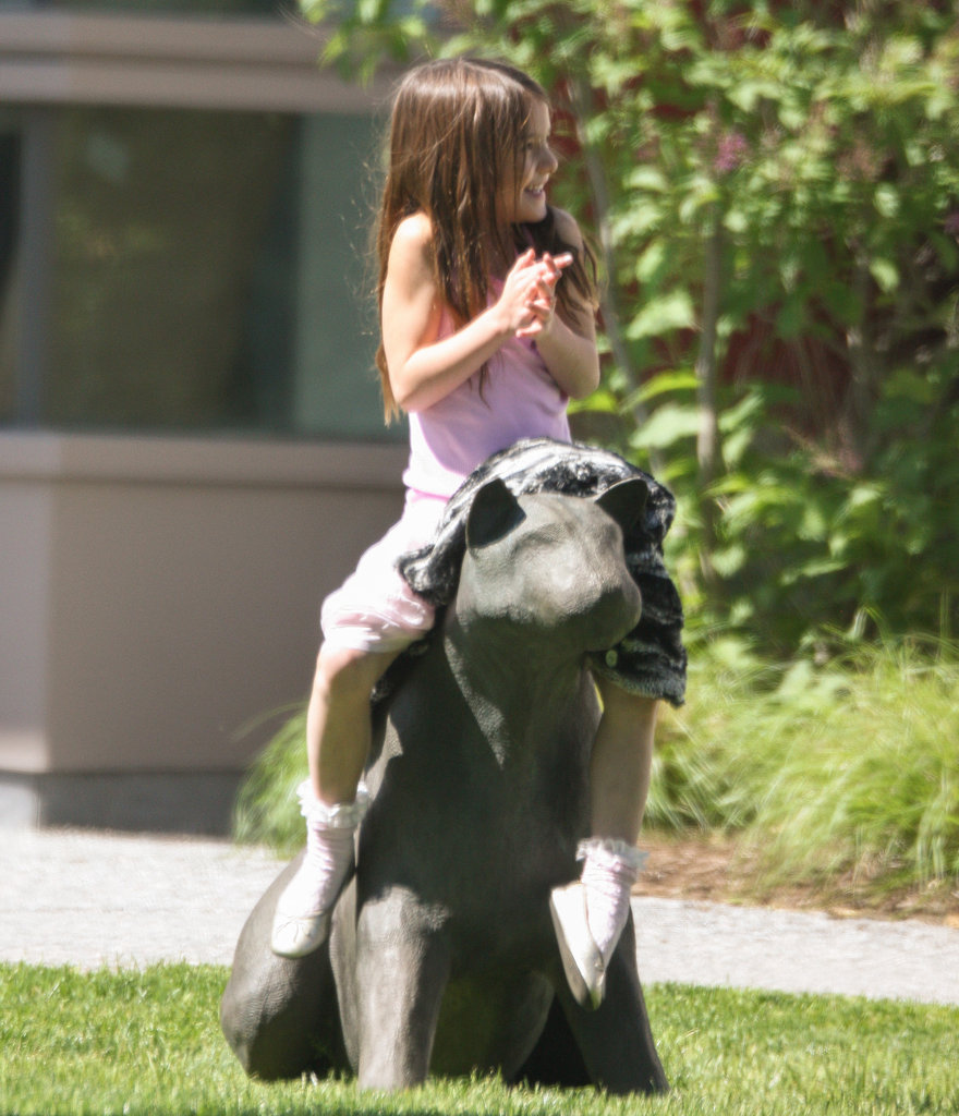 Suri Cruise hopped on a park statue.