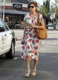 On a coffee run in LA, Eva wore a Free People rose-print dress with wedge sandals, a tan hobo bag, and oversized shades.  6935546