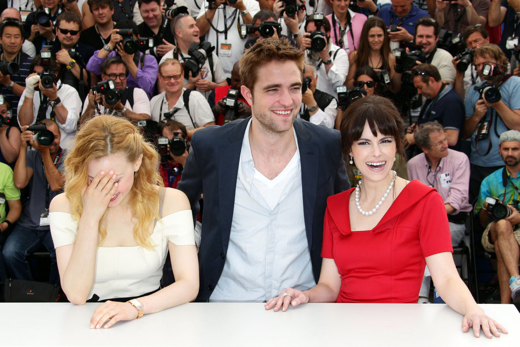 Robert Pattinson had his costars Sarah Gadon and Emily Hampshire laughing at the Cosmopolis photocall in Cannes.