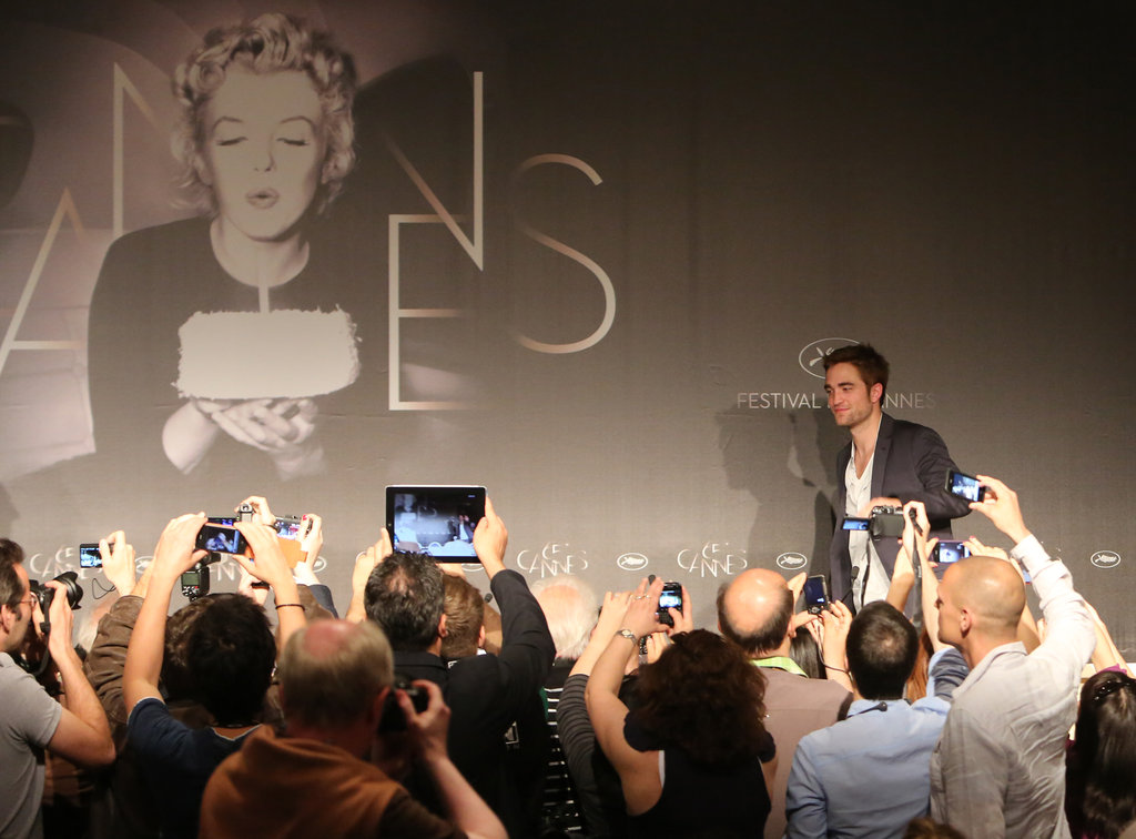 Robert Pattinson walked onstage at the Cosmopolis photocall in Cannes.