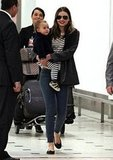 Miranda Kerr toted baby Flynn through the airport in a striped top with skinny jeans, a black jacket, a laid-back flats.