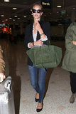 Rosie Huntington-Whiteley took running through the airport to a chic new level with her pairing of dark skinny jeans, a fitted blazer, and sleek black flats.
